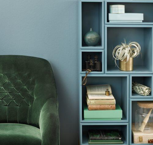 grønn stol med blå vegg bak