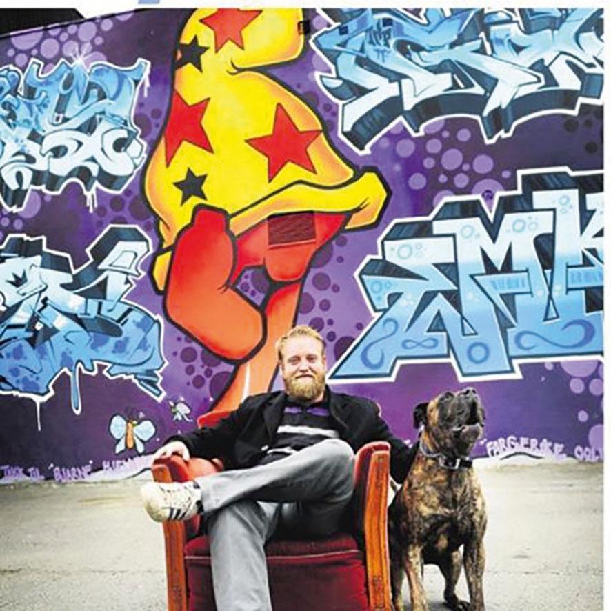 mann i stol foran grafittivegg