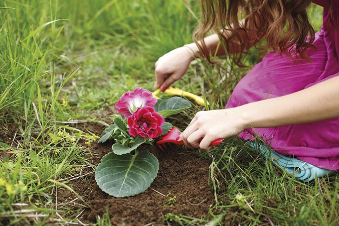 jente som planter en blomst