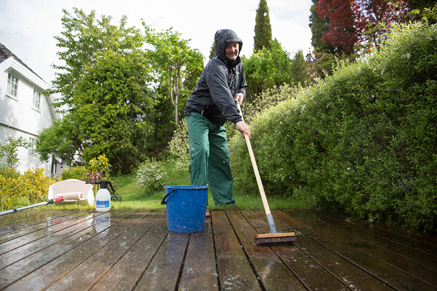 mann som vasker terrassen