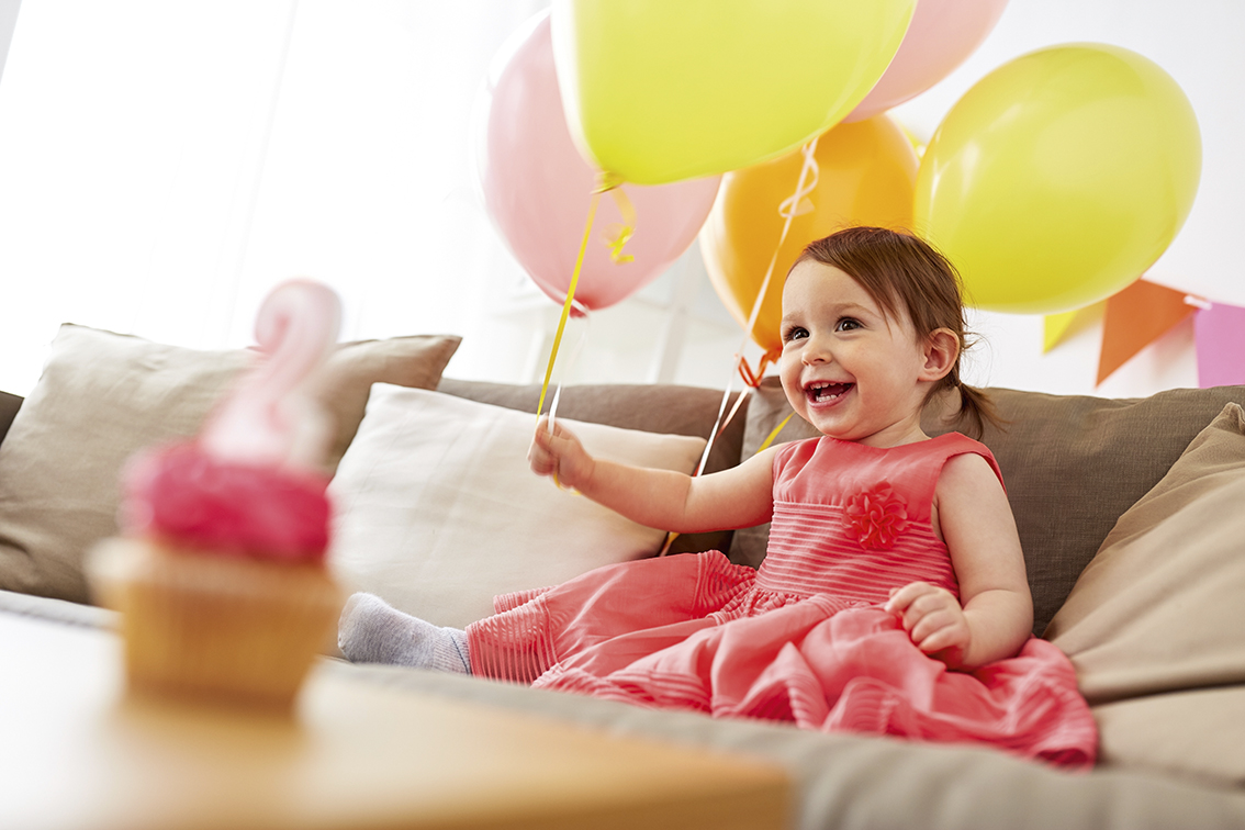 childhood, holidays and people concept - happy baby girl with air balloons, garland and cupcake on birthday party at home